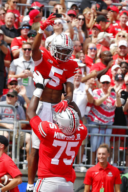 Ohio State receiver Garrett Wilson, top, celebrates his touchdown against Oregon with teammate offensive lineman Thayer Munford during the first half of an NCAA college football game Saturday, Sept. 11, 2021, in Columbus, Ohio. (AP Photo/Jay LaPrete)