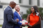Brittney Payton, daughter of former Chicago Bears and Pro Football Hall of Fame running back Walter Payton, right, and her brother Jarrett, left, present sculptor Chad Fisher with a gift during an unveiling ceremony outside Soldier Field of statues honoring George Halas and their father Tuesday, Sept. 3, 2019, in Chicago. (AP Photo/Charles Rex Arbogast)