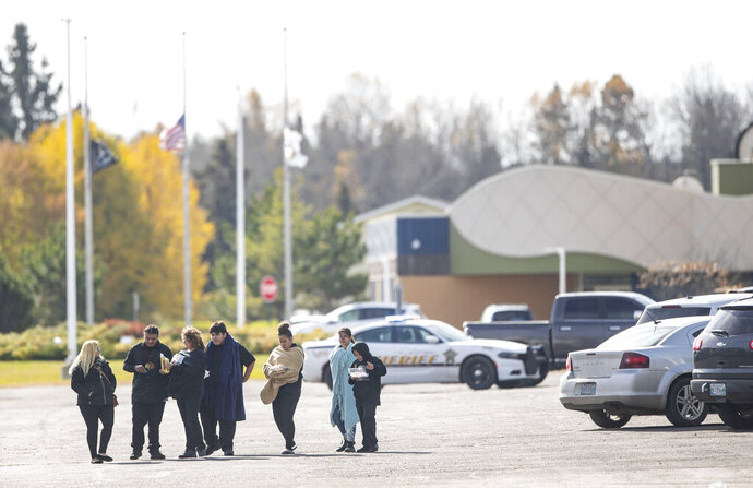 People walked away from the community center on the Fond Du Lac Band reservation near Cloquet, Minn., Friday, Oct. 18, 2019, after the lockdown was lifted. One man was shot and a suspect was arrested after a shooting Friday on an American Indian reservation in northern Minnesota that prompted a lockdown of tribal offices and a school. (Alex Kormann/Star Tribune via AP)