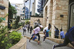FILE - In this Tuesday, Jan. 15, 2019 file photo, civilians flee as security forces aim their weapons at a luxury hotel complex attacked by the al-Shabab extremist group, in Nairobi, Kenya. U.N. experts said in a report circulated Tuesday, Nov. 12, 2019 that al-Shabab extremists in Somalia remain