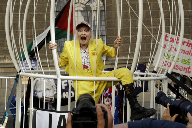 Fashion designer Vivienne Westwood stands in a giant bird cage in protest against the extradition of WikiLeaks founder Julian Assange to the U.S., outside the Old Bailey court, in London, Tuesday, July 21, 2020. Assange is in London's Belmarsh Prison awaiting a full extradition hearing, which has been postponed because of the coronavirus pandemic. Originally due to begin in May, it is now scheduled to start on Sept. 7 at the Old Bailey. (AP Photo/Matt Dunham)