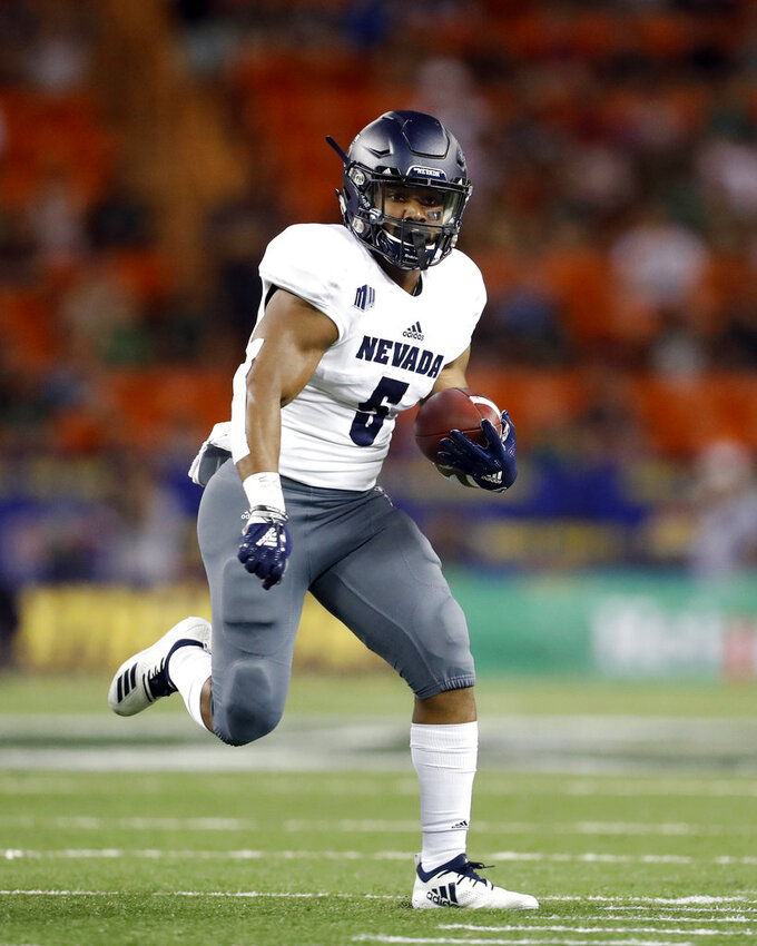Nevada running back Jaxson Kincaide (5) runs through the Hawaii defensive line during the second quarter of an NCAA college football game, Saturday, Oct. 20, 2018, in Honolulu. (AP Photo/Marco Garcia)