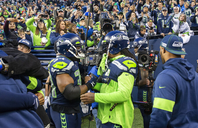 Newly signed running backs and former Seahawks teammates Robert Turbin, left, and Marshawn Lynch embrace during warmups at CenturyLink Field in Seattle on Sunday, Dec. 29, 2019. (Drew Perine/The News Tribune via AP)