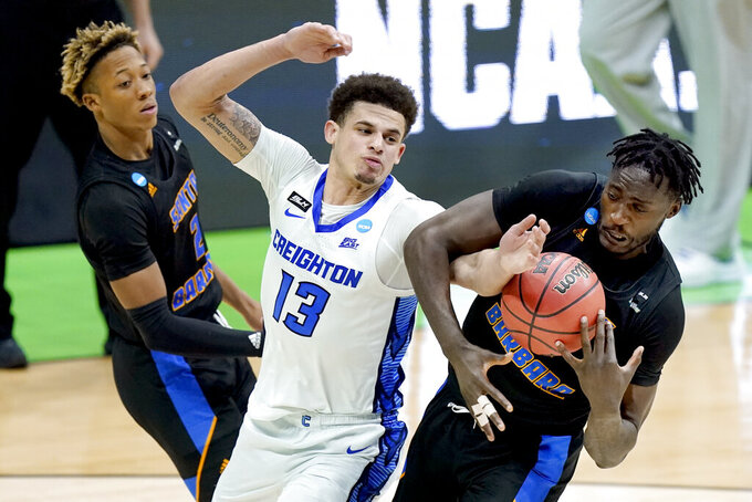 Creighton's Christian Bishop (13) battles for the ball with UC Santa Barbara's Robinson Idehen, right,during the second half of a college basketball game in the first round of the NCAA tournament at Lucas Oil Stadium in Indianapolis Saturday, March 20, 2021. (AP Photo/Mark Humphrey)