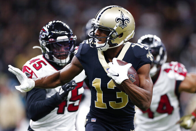 New Orleans Saints wide receiver Michael Thomas (13) carries on a pass reception ahead of Atlanta Falcons linebacker Deion Jones (45) and defensive end Vic Beasley (44) in the first half of an NFL football game in New Orleans, Sunday, Nov. 10, 2019. (AP Photo/Rusty Costanza)