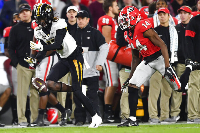 Missouri wide receiver Kam Scott (13) can't keep hands on a pass as Georgia defensive back DJ Daniel defends during the first half of an NCAA college football game Saturday, Nov. 9, 2019, in Athens, Ga. (AP Photo/John Amis)