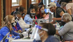 Poll workers prepare voters for the machines on Tuesday, Aug.  11, 2020  during the Georgia Primary in Atlanta. (John Spink/Atlanta Journal-Constitution via AP)