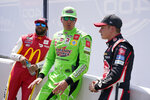 Kyle Busch, center, talks with Bubba Wallace, left, and Christopher Bell before player introductions at the NASCAR Cup Series auto race at Michigan International Speedway, Sunday, Aug. 22, 2021, in Brooklyn, Mich. (AP Photo/Carlos Osorio)