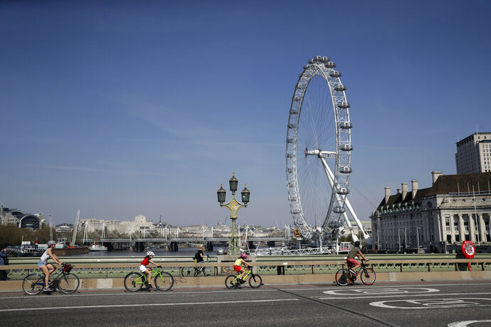 A family space themselves apart as they cycle over Westminster Bridge past the London Eye ferris wheel in London, Friday, April 10, 2020. In a statement Thursday, a spokesman at 10 Downing Street said British Prime Minister Johnson
