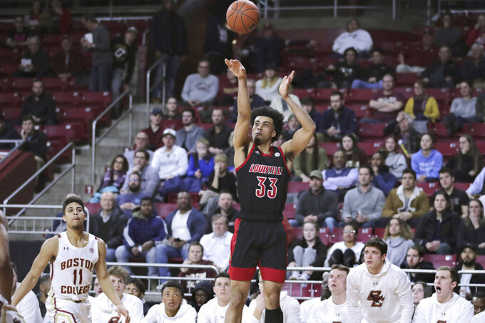 Louisville forward Jordan Nwora (33) shoots as Boston College players watch during the first half of an NCAA college basketball game in Boston, Wednesday, Jan. 29, 2020. (AP Photo/Charles Krupa)