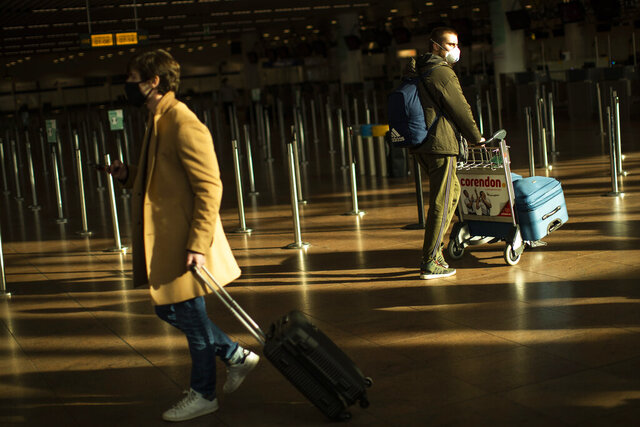 Travellers, wearing face masks to prevent the spread of the coronavirus COVID-19, walk along the departure hall of the Zaventem international airport in Brussels, Friday, Jan. 22, 2021. European Union nations are searching ways to contain the pandemic and several are looking to limit non essential travels for the next weeks. Belgium has been at the forefront of that fight and authorities will decide late Friday whether to ban all leisure travel for a month. (AP Photo/Francisco Seco)