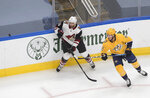 Arizona Coyotes' Alex Goligoski (33) and Nashville Predators' Ryan Johansen (92) chase a loose puck during the first period of NHL qualifying round game action in Edmonton, Alberta, Tuesday, Aug. 4, 2020.  (Jason Franson/The Canadian Press via AP)