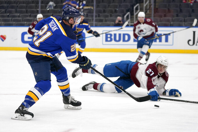 St. Louis Blues' Tyler Bozak (21) shoots as Colorado Avalanche's Ryan Graves (27) defends during the second period of an NHL hockey game Thursday, April 22, 2021, in St. Louis. (AP Photo/Jeff Roberson)