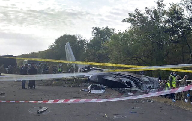 In this photo provided by the Emergency Situation Ministry, a view of the debris and remains of the AN-26 military plane  which crashed on Friday night, in the town of Chuguyiv close to Kharkiv, Ukraine, Saturday Sept. 26, 2020. Searchers combing the area where a Ukrainian military aircraft crashed found two more bodies on Saturday, bringing the death toll to 26. One person survived. The plane, a twin-turboprop Antonov-26 belonging to the Ukrainian air force, was carrying a crew of seven and 20 cadets of a military aviation school when it crashed and burst into flames Friday night while coming in for landing at the airport in Chuhuiv, about 400 kilometers (250 miles) east of the capital Kyiv.  (Emergency Situation Ministry via AP)
