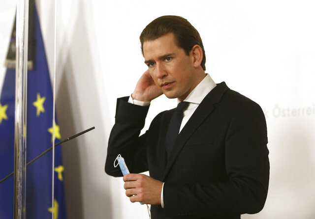Austrian Chancellor Sebastian Kurz holds his a face mask behind plexiglass shields before a media conference as they commemorate the terror attack one week ago, at the federal chancellery in Vienna, Austria, Monday, Nov. 9, 2020.  Several shots were fired shortly after 8 p.m. local time on Monday, Nov. 2, in a lively street in the city centre of Vienna. (AP Photo/Ronald Zak)