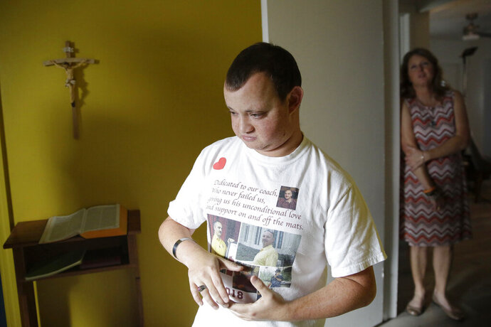 "Corey Hixon, 24, wears a shirt with photographs of his father, Chris Hixon, as his mother, Debbi Hixon, stands in the doorway on Friday, Feb. 14, 2020, in Hollywood, Fla. Chris Hixon was killed in the school shooting on Valentine's Day two years ago at Marjory Stoneman Douglas High School in Parkland, Fla. ""He's still part of our family and i didn't want it to feel like he's not here anymore,"" she said of the home renovation completed during a whirlwind 10-days for the show ""Military Makeovers."" (AP Photo/Brynn Anderson)"