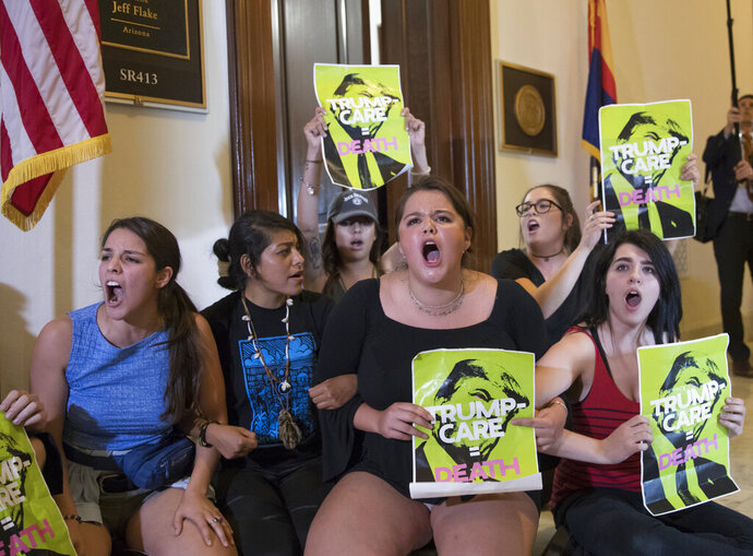 FILE - In this July 10, 2017, file photo, activists protest against the Republican health care bill outside the offices of Sen. Jeff Flake, R-Ariz., and Sen. Ted Cruz, R-Texas on Capitol Hill in Washington. Arizona has quietly suspended its plans to require that about 120,000 people receiving Medicaid benefits work, volunteer or go to school. The state Medicaid program posted a notice on its website saying the work requirements are being delayed