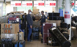 People check in luggages at the Vaclav Havel airport after a Russian special government plane landed in Prague, Czech Republic, Monday, April 19, 2021. Czech Republic is expelling 18 diplomats identified as spies over a 2014 ammunition depot explosion. On Saturday, April 17, 2021, Prime Minister Andrej Babis said the Czech spy agencies provided clear evidence about the involvement of Russian military agents in the massive explosion that killed two people. (AP Photo/Petr David Josek)