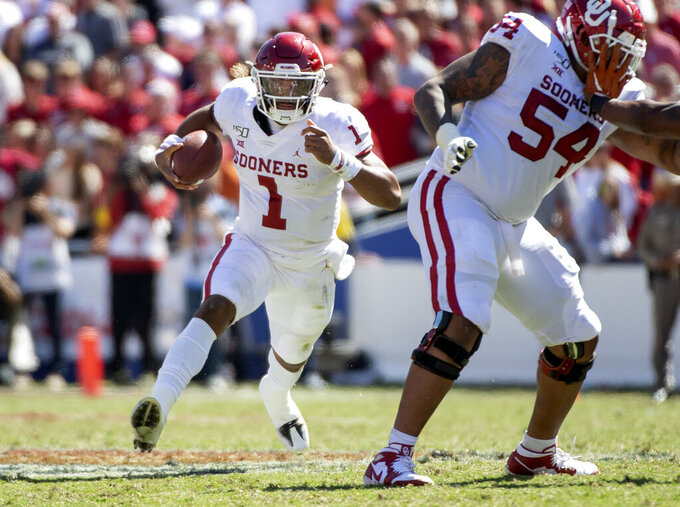 Oklahoma quarterback Jalen Hurts (1) runs against Texas behind the block of offensive lineman Marquis Hayes (54) in the second half of an NCAA college football game at the Cotton Bowl, Saturday, Oct. 12, 2019, in Dallas. Oklahoma won 34-27. (AP Photo/Jeffrey McWhorter)