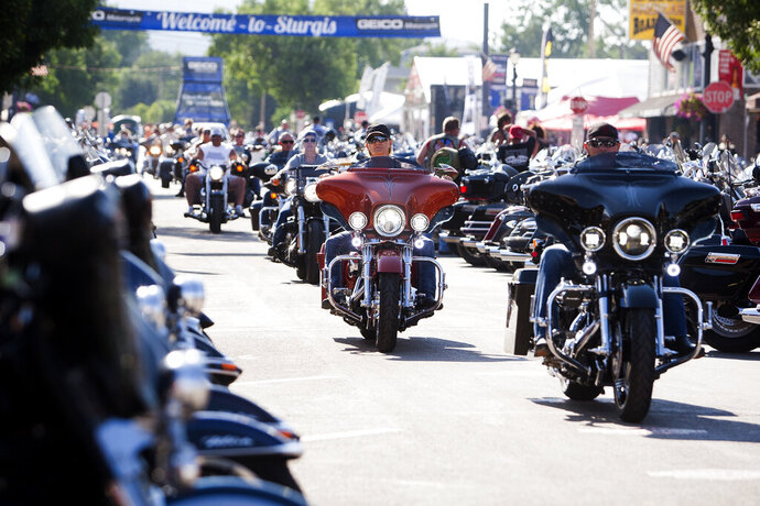 FILE - In this Aug. 5, 2016 file photo, bikers ride down Main Street in downtown Sturgis, S.D., before the 76th Sturgis motorcycle rally officially begins.  South Dakota, which has seen an uptick in coronavirus infections in recent weeks, is bracing to host hundreds of thousands of bikers for the 80th edition of the Sturgis Motorcycle Rally. Over a quarter of a million people are expected to rumble through western South Dakota. (Josh Morgan/Rapid City Journal via AP, File)
