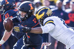 Illinois quarterback Matt Robinson (12) is taken down by Michigan's Josh Ache (6) in the second half of an NCAA college football game, Saturday, Oct. 12, 2019, in Champaign, Ill. (AP Photo/Holly Hart)