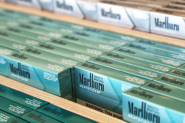 FILE - This Nov. 25, 2019 photo shows IQOS heated cigarette heatsticks displayed in an IQOS store in Richmond, Va.  Marlboro cigarettes pushed tobacco company Altria's revenue higher in the last quarter. But company results were weighed down by charges across its sprawling business, which also includes e-cigarettes, beer and wine. (AP Photo/Steve Helber, File)