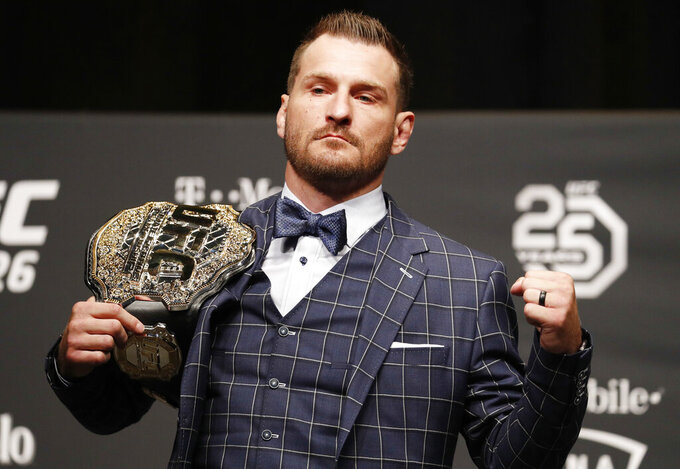 FILE - In this July 5, 2018, file photo, Stipe Miocic poses during a news conference for UFC 226 in Las Vegas. Heavyweight champion Stipe Miocic welcomes the UFC's planned return. The fighter and firefighter does have some worries, though. (AP Photo/John Locher, File)