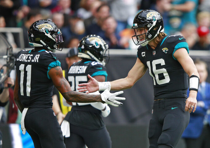 Jacksonville Jaguars quarterback Trevor Lawrence (16) celebrates with Jacksonville Jaguars wide receiver Marvin Jones (11) after they combined to score a touchdown during the first half of an NFL football game between the Miami Dolphins and the Jacksonville Jaguars at the Tottenham Hotspur stadium in London, England, Sunday, Oct. 17, 2021. (AP Photo/Ian Walton)