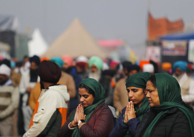 Women farmers pray during a gathering in protest against new farm laws at the Delhi-Haryana state border, on the outskirts of New Delhi, India, Sunday, Dec. 27, 2020. From students, teachers and nurses to housewives and grandmothers, women are now holding the front lines at the massive protests that have blockaded key highways leading to India's capital for more than a month, demanding the repeal of new farm laws. (AP Photo/Manish Swarup)