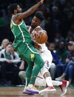 Philadelphia 76ers' Jimmy Butler, right, fouls Boston Celtics' Kyrie Irving during the first half of an NBA basketball game in Boston, Tuesday, Dec. 25, 2018. (AP Photo/Michael Dwyer)
