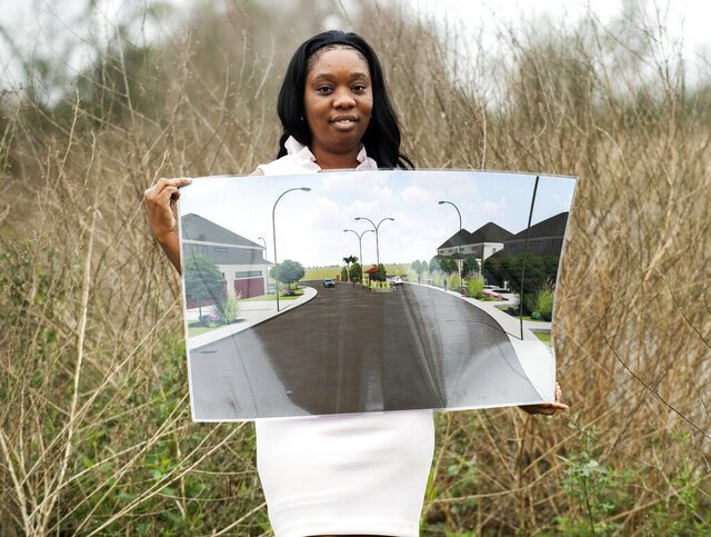 In this Monday, Jan. 27, 2020 photo, project developer Terrica Smith holds a rendering of the planned Madeline Cove subdivision, at the site in Lafayette, La. (Leslie Westbrook/The Advocate via AP)