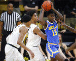 UCLA guard Kris Wilkes, right, passes the ball as Colorado guards D'Shawn Schwartz, center, and Tyler Bey defend in the second half of an NCAA college basketball game Thursday, March 7, 2019, in Boulder, Colo. (AP Photo/David Zalubowski)