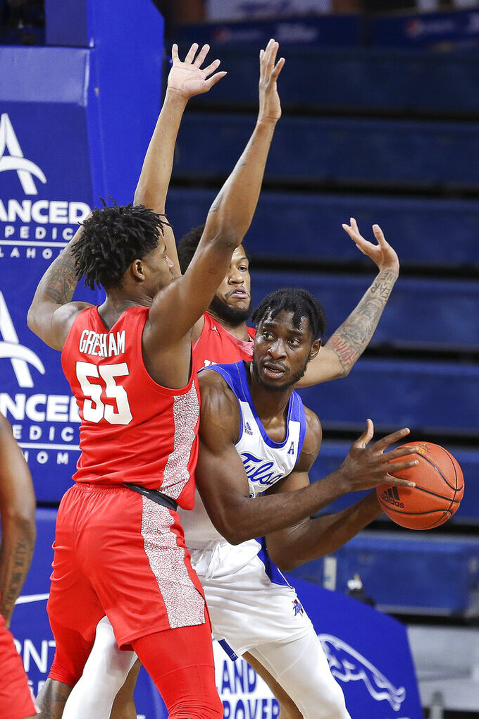Tulsa's Emmanuel Ugboh looks to pass while guarded by Houston's Brison Gresham (55) and Justin Gorham during the first half of an NCAA college basketball game in Tulsa, Okla., Tuesday, Dec. 29, 2020. (AP Photo/Dave Crenshaw)