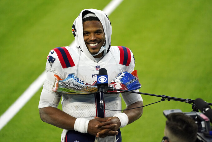 New England Patriots quarterback Cam Newton smiles as he conducts an interview at the end of an NFL football game against the Los Angeles Chargers Sunday, Dec. 6, 2020, in Inglewood, Calif. (AP Photo/Ashley Landis)