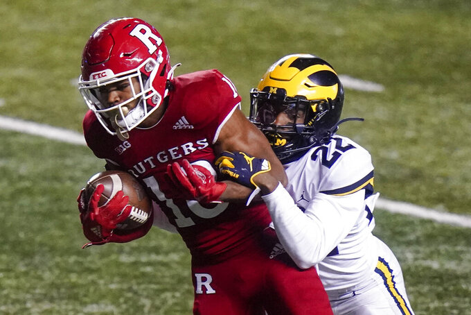 Michigan's Gemon Green, right, tackles Rutgers' Bo Melton during the third overrtime of an NCAA college football game Sunday, Nov. 22, 2020, in Piscataway, N.J. Michigan won 48-42. (AP Photo/Frank Franklin II)