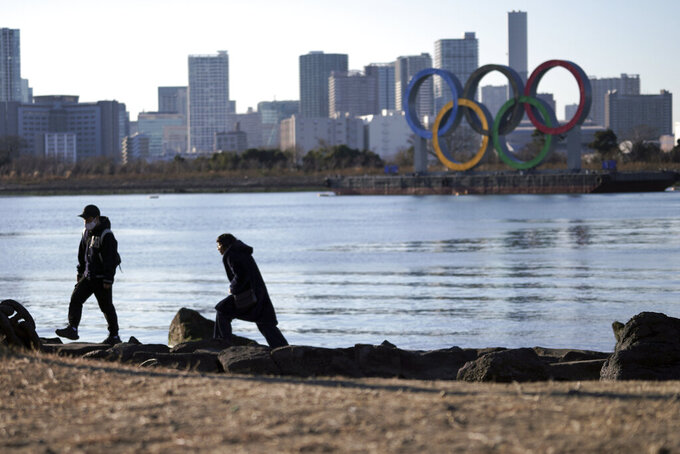 A man and a woman walk near the Olympic rings floating in the water in the Odaiba section in Tokyo Wednesday, Jan. 20, 2021. The postponed Tokyo Olympics are to open in just six months. Local organizers and the International Olympic Committee say they will go ahead on July 23. But it's still unclear how this will happen with virus cases surging in Tokyo and elsewhere around the globe. (AP Photo/Eugene Hoshiko)