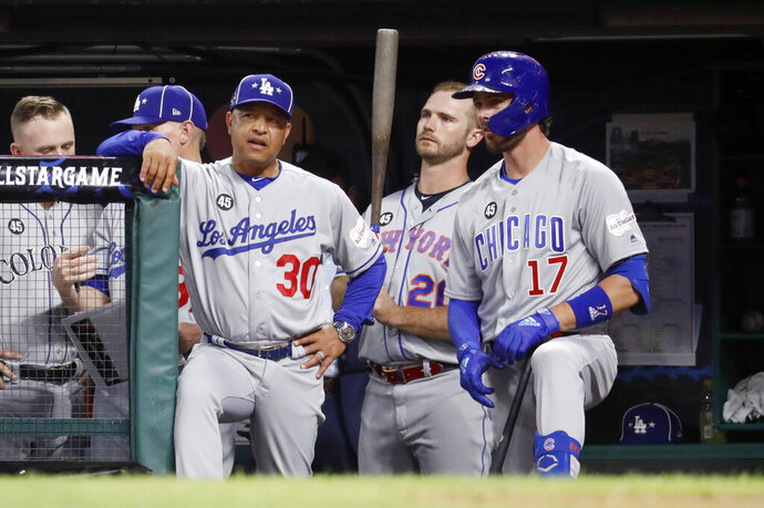 National League manager Dave Roberts (30), of the Los Angeles Dodgers, talks with National League Kris Bryant (17), of the Chicago Cubs, during the fifth inning of the MLB baseball All-Star Game against the American League, Tuesday, July 9, 2019, in Cleveland. (AP Photo/John Minchillo)