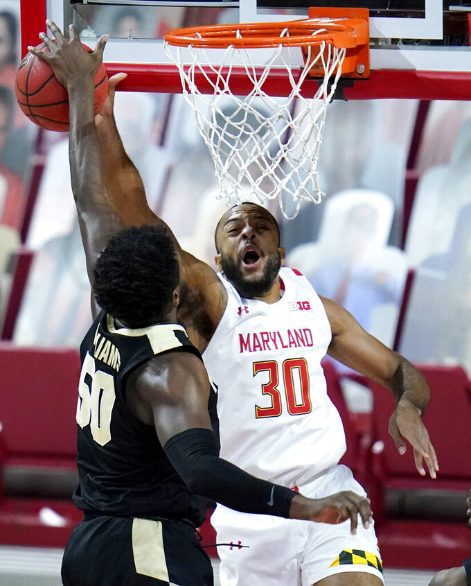 Purdue forward Trevion Williams (50) blocks a shot by Maryland forward Galin Smith (30) during the first half of an NCAA college basketball game, Tuesday, Feb. 2, 2021, in College Park. (AP Photo/Julio Cortez)