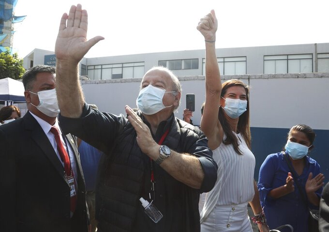 Avanza Pais party presidential candidate Hernando De Soto and his wife Carla Olivieri, wave to supporters upon their arrival to vote during general elections in Lima, Peru, Sunday, April 11, 2021. (AP Photo/Martin Mejia)