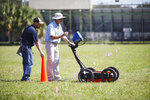 FILE- In this Oct. 23, 2019 file photo, Scott Purcell, a senior geophysicist with GeoView, left, and Mike Wightman, president of GeoView use ground penetrating radar technology to scan a portion of King High School campus in search for Ridgewood Cemetery in Tampa, Fla. School officials say ground penetrating radar has located 145 graves on the ground of the high school. The Florida Senate set aside $100,000 in its budget proposal to erect memorials at Zion and Ridgewood cemeteries in Tampa. Both were African Americas cemeteries that were abandoned and in some cases the land was developed on top of burial sites. (Octavio Jones/Tampa Bay Times via AP, File)
