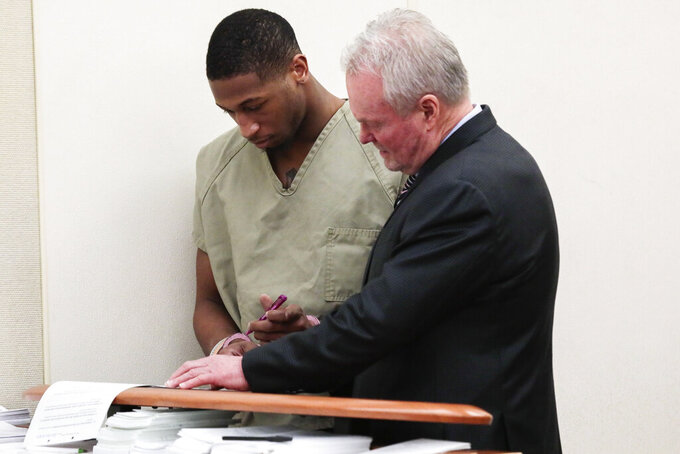Former Ohio State Buckeyes football player Amir Riep signs paperwork with the assistance of his attorney, Karl Schneider, right, during his arraignment on Thursday, Feb. 13, 2020, at the Franklin County Municipal Courthouse in Columbus, Ohio. Riep, who was dismissed from the team on Feb. 12, 2020 ,along with teammate and co-defendant Jahsen Wint, are charged with the rape and kidnapping of a 19-year-old woman on Feb. 4, 2020 at an apartment the two men share. (Joshua A. Bickel/The Columbus Dispatch via AP)