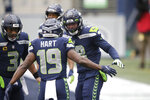 Seattle Seahawks' Freddie Swain, right, celebrates his touchdown with teammates Penny Hart (19) and Russell Wilson (3) during the first half of an NFL football game against the New York Jet, Sunday, Dec. 13, 2020, in Seattle. (AP Photo/Lindsey Wasson)