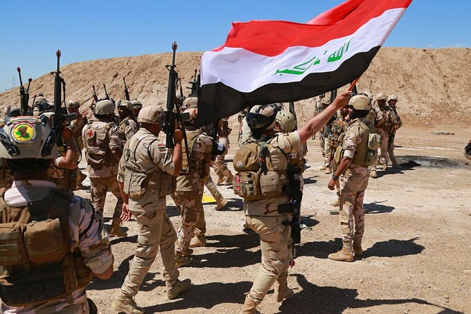 FILE - In this April 17, 2019, file photo, Iraqi soldiers chant slogans against IS while Australian and New Zealand coalition forces participate in a training mission with Iraqi army soldiers at Taji Base, north of Baghdad, Iraq. In a quest to root out Islamic State group hideouts over the summer, Iraqi forces on the ground cleared nearly 90 villages across a notoriously unruly northern province. But the much-touted operation still relied heavily on U.S. intelligence, coalition flights and planning assistance. (AP Photo/Hadi Mizban, File)
