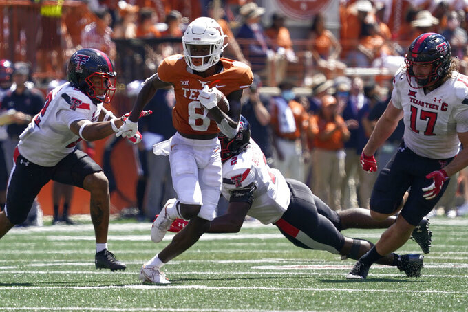 Texas wide receiver Xavier Worthy (8) runs past Texas Tech's Colin Schooler (17), Reggie Pearson Jr. (22) and Brandon Bouyer-Randle (2) for a touchdown during the second half of an NCAA college football game on Saturday, Sept. 25, 2021, in Austin, Texas. (AP Photo/Chuck Burton)