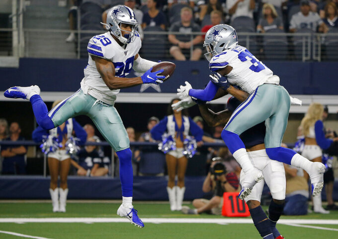 Dallas Cowboys defensive back C.J. Goodwin (29) intercepts a pass intended for Houston Texans' Tyron Johnson, right rear, with help on defense by Donovan Wilson, right front, in the first half of a preseason NFL football game in Arlington, Texas, Saturday, Aug. 24, 2019. (AP Photo/Michael Ainsworth)