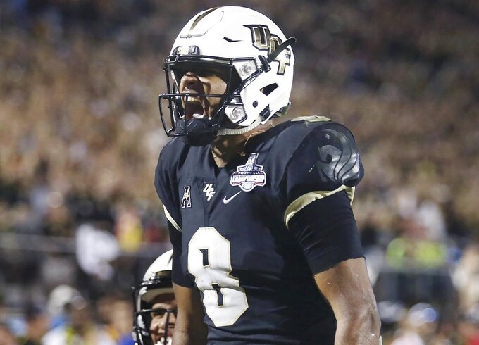 UCF quarterback Darriel Mack Jr. celebrates after he scored a fourth quarter touchdown during an NCAA college football game in the AAC Championship in Orlando on Saturday, Dec. 1, 2018. UCF won the game to claim the AAC Championship. (Stephen M. Dowell/Orlando Sentinel via AP)
