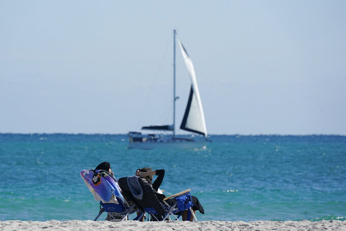 FILE - In this Dec. 1, 2020 file photo, beachgoers enjoy a chilly day at the beach as a sailboat passes by in Miami Beach, Fla. Vacation home rentals are increasingly popular among travelers, especially during the pandemic. The problem for many savvy travelers is that it's hard to use rewards points to cover the rental cost.   (AP Photo/Wilfredo Lee, File)