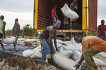 FILE - In this Thursday, June 26, 2014 file photo, workers offload sacks of cereals from the World Food Program (WFP) from a truck in Minkaman, South Sudan. The World Food Program on Friday, Oct. 9, 2020 won the 2020 Nobel Peace Prize for its efforts to combat hunger and food insecurity around the globe. (AP Photo/Matthew Abbott, File)