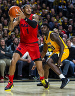 Dayton forward Obi Toppin (1) holds the ball as VCU guard Vince Williams (10) plays defense during the first half of an NCAA college basketball game, Tuesday, Feb. 18, 2020, in Richmond, Va. (AP Photo/Zach Gibson)