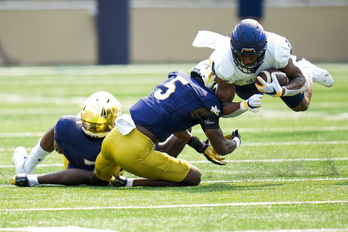 Toledo running back Micah Kelly, right, is tackled by Notre Dame cornerback Cam Hart (5) in the first half of an NCAA college football game in South Bend, Ind., Saturday, Sept. 11, 2021. (AP Photo/AJ Mast)